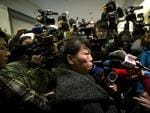 A Chinese relative of passengers aboard a missing Malaysia Airlines plane is surrounded by media as she answers questions about how families are being compensated outside a hotel room. Picture: AP