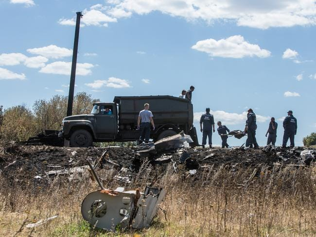 Personnel from the Ukrainian Emergencies Ministry load the bodies of victims of Malaysia Airlines flight MH17 into a truck at the crash site on July 21, 2014 in Grabovo, Ukraine. Picture: Getty