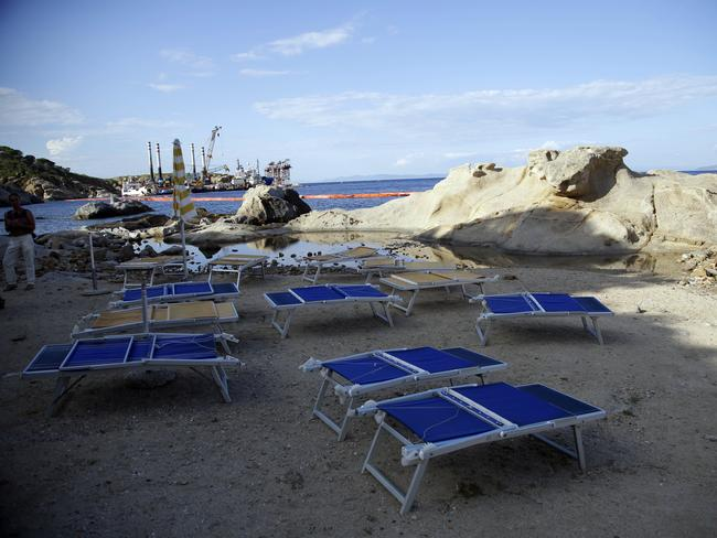 Sunbeds lined up on a beach on the Tuscan island of Giglio, Italy, where people watched the ship.