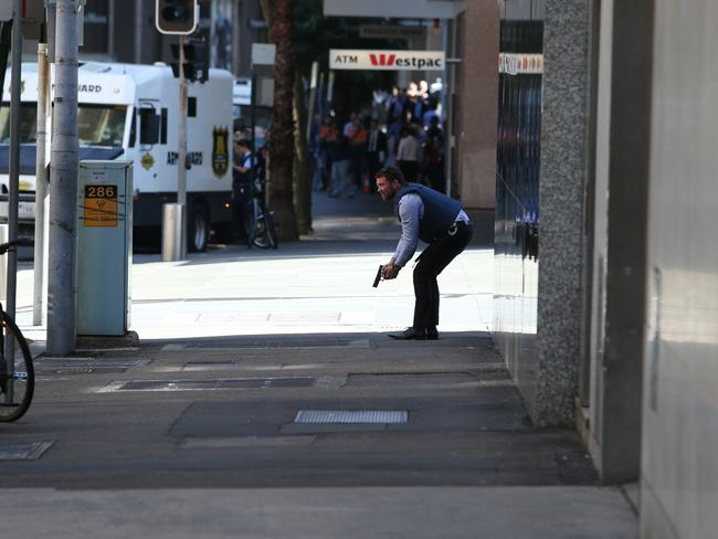 City on lockdown ... A police officer with gun drawn in the Sydney CBD.