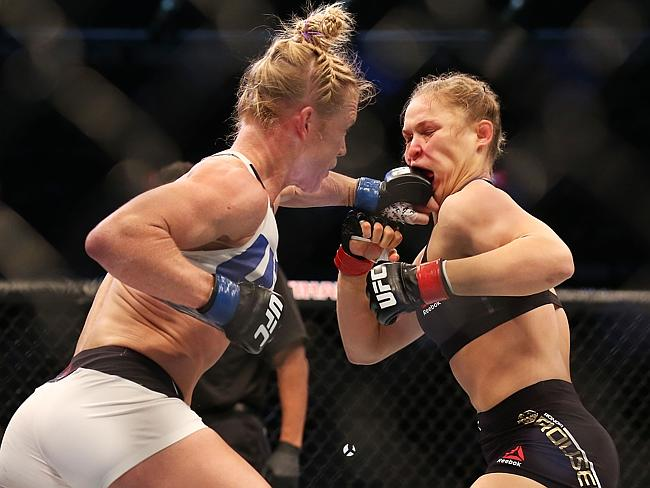 Ronda Rousey eats a punch from Holly Holm during their UFC 193 fight.