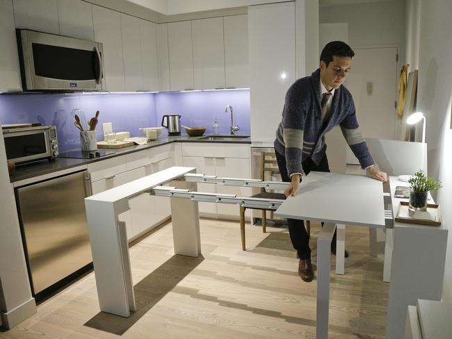 Stage 3 Properties co-founder Christopher Bledsoe demonstrates a desk that expands into a dining table that can seat up to 12 people. Picture: Julie Jacobson
