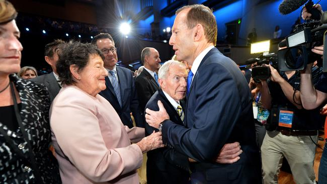 Mr Abbott gives his dad a hug on the campaign trail in 2013. Mr Abbott senior's wife, Fay, looks on.
