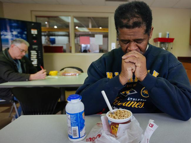 James Robertson, 56, prays before eating in the break room of the factory he walks 33km to each day.