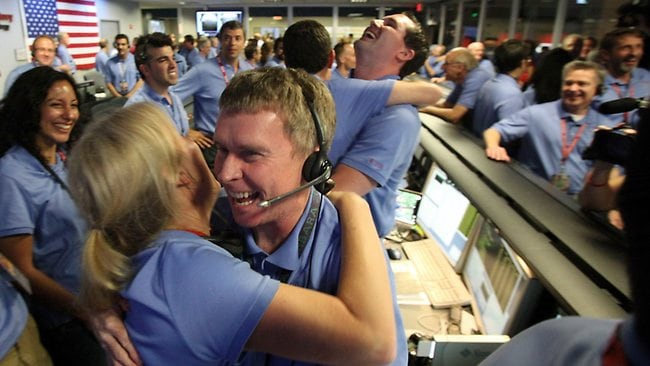 Telecom engineer Peter Ilott (centre) hugs a colleague, celebrating a successful landing inside the Spaceflight Operations Facility for NASA's Mars Science Laboratory Curiosity rover at Jet Propulsion Laboratory (JPL) in Pasadena, California. Picture: AFP