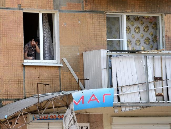 A woman reacts as she stands at her window with broken panes in downtown Donetsk. Picture: Francisco Leong