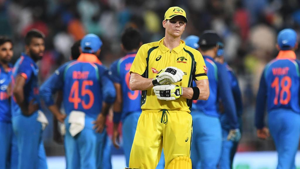 Australia's captain Steve Smith (C) reacts as Indian cricketers celebrate the wicket of Australia's Travis Head during the second one day international (ODI) match of the ongoing India-Australia cricket series at the Eden Gardens Cricket Stadium in Kolkata on September 21, 2017. / AFP PHOTO / Dibyangshu SARKAR / ----IMAGE RESTRICTED TO EDITORIAL USE — STRICTLY NO COMMERCIAL USE----- / GETTYOUT