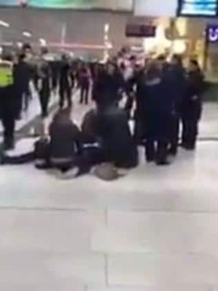 Commuters rush to the aid of an injured person on the floor of the Dusseldorf train station in Germany. Picture: Twitter.