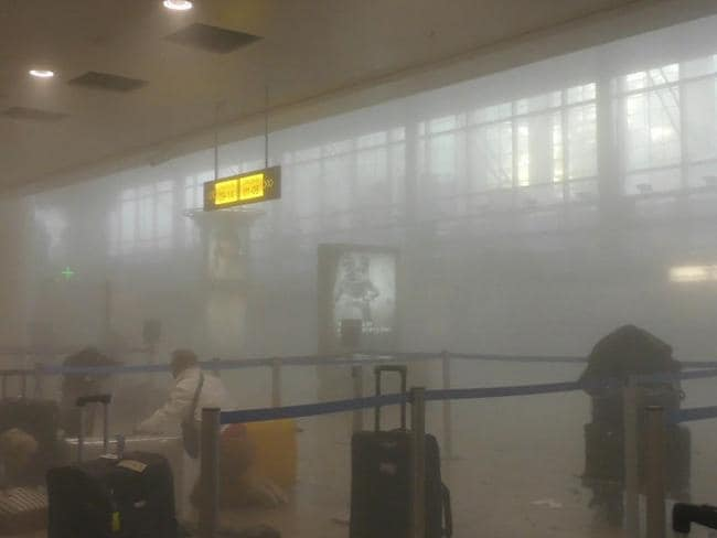 An unidentified traveller gets to his feet in a smoke filled terminal at Brussels Airport. Picture: Ralph Usbeck via AP