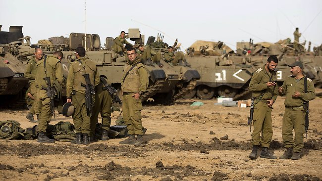 Israeli soldiers gather next to their armoured personnel carriers stationed on Israel's border with the Gaza Strip. Picture: AFP