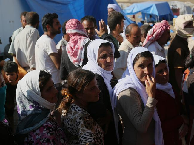 Relief ... Displaced Iraqis from the Yazidi community gather for humanitarian aid at Nowruz camp, in Derike, Syria.