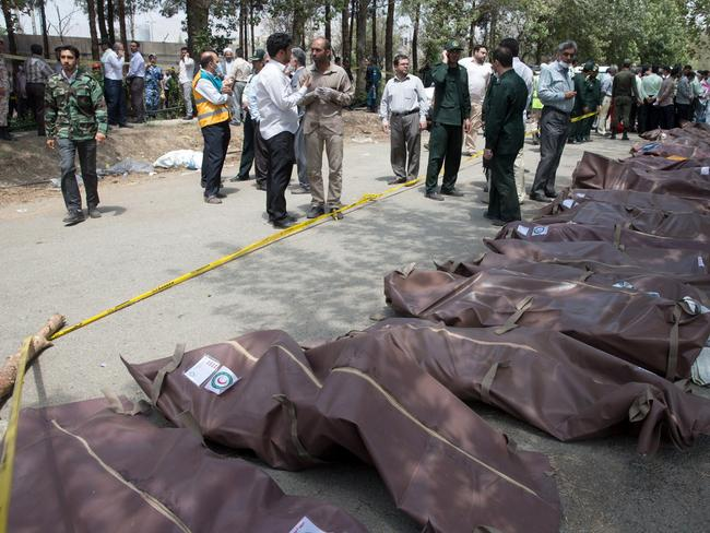Grim scene ... The bodies of victims wrapped in plastic bags at the scene of an Iranian plane crash. Picture: Rouhollah Vahdati