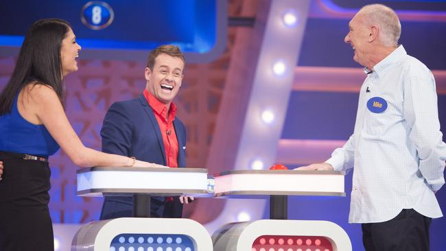 Grant Denyer shares a laugh with contestants Dimitra Kavadias and Mike Hammond on  <i>Family Feud</i>.
