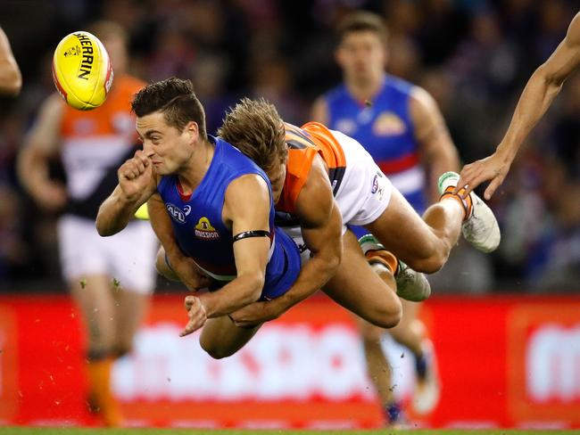 Luke Dahlhaus of the Bulldogs is tackled by Matt de Boer of the Giants. Picture: Adam Trafford