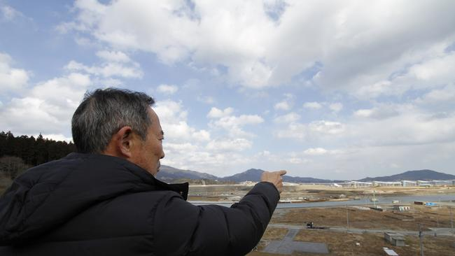 Local leader Takeshi Konno points at a construction site for the giant sea walls.