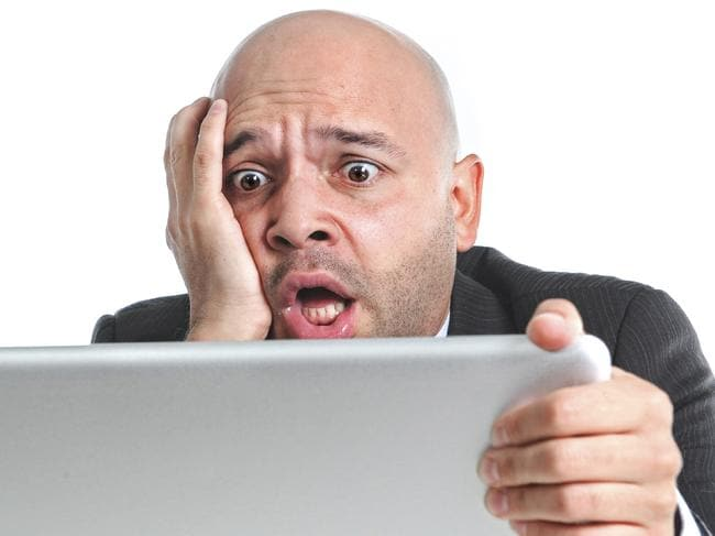 businessman in crisis and stress at computer laptop holding monitor watching online finances drop down or loosing money internet gambling isolated on white background
