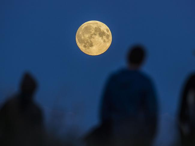 People watch a full moon rising in Berlin. Picture: AP Photo/Gero Breloer