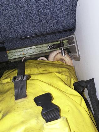 The snake lies beneath a duffel bag. Picture: Anna McConnaughy via AP