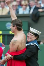 <p>Naval steward apprehending naked male streaker streaking during mens singles final match at Wimbledon Championships 07 Jul 2002.</p>