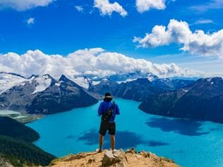 Rear View Of Man Standing On Panorama Ridge Overlooking Garibaldi Lake In Garibaldi Provincial Park