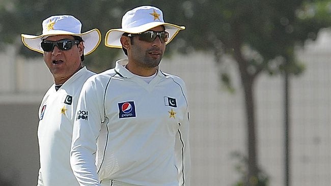 Pakistan's cricket captain Misbah-ul Haq walks past coach Mohsin Khan (L).