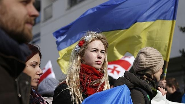 A woman wearing a traditional Ukrainian headband demonstrates outside the Russian Embassy in Paris.