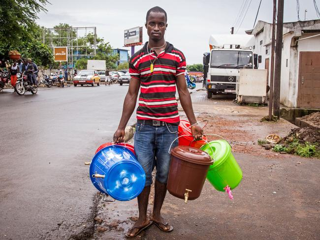 A street trader in Freetown sells buckets as demand has boomed for sanitation products during the Ebola crisis. Pic: AP.