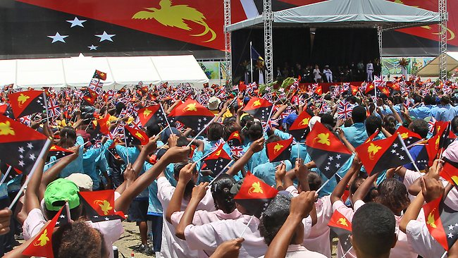 Royal Tour of PNG: thousands of children wave flags while performing for Charles and Camilla during a cultural display in Port Moresby.