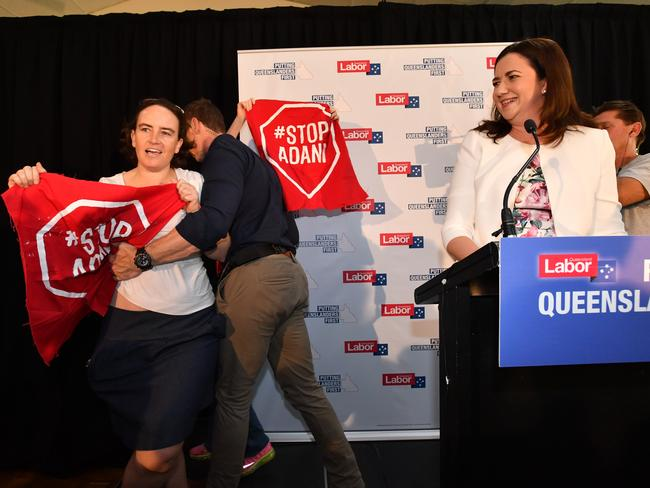 Anti-Adani coal mine protesters invade the stage as Queensland Premier Annastacia Palaszczuk (right) delivers her speech after announcing the date of the Queensland Election at Cementco Bowls Club in Brisbane on Sunday. Picture: Darren England/AAP