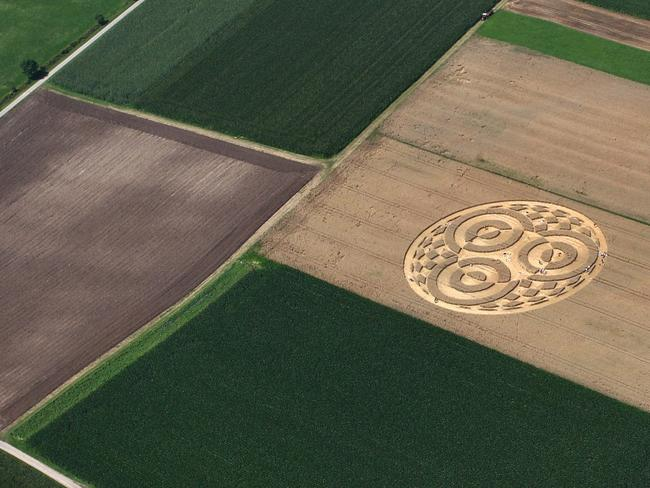 People walk through crop circles shaped into a cornfield near Raisting, southern Germany. Picture: Karl-Josef Hildenbrand