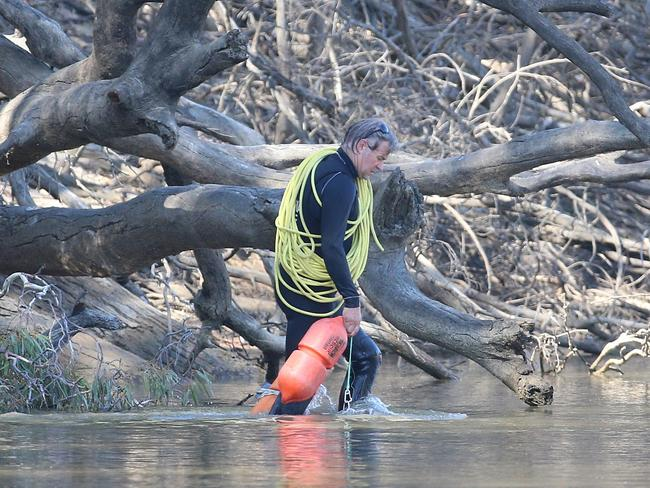 Victorian police divers search the Murray River for the missing five-year-old boy. Picture: Hamish Blair
