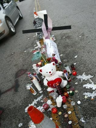 Tragic scene ... A makeshift memorial sits in the middle of the street where 18-year-old Michael Brown was shot and killed by police. Source: AP