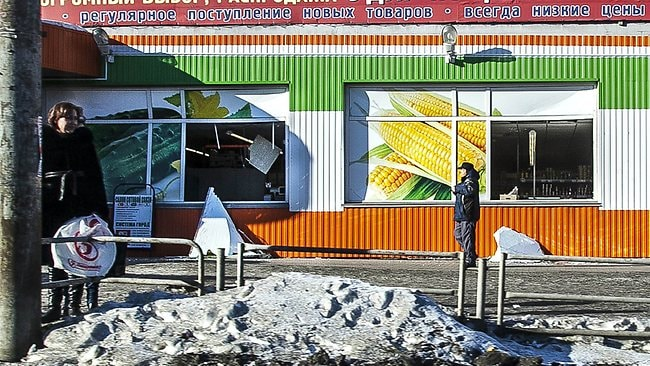 People stand in front of the facade of a local shop which was damaged by a shockwave from a meteor in the Urals city of Chelyabinsk, on February 15, 2013. A meteor strike in central Russia that left today hundreds of people injured is the biggest known human toll from a space rock, a British expert said. AFP PHOTO / 74.RU/ OLEG KARGOPOLOV --BEST QUALITY FROM SOURCE--