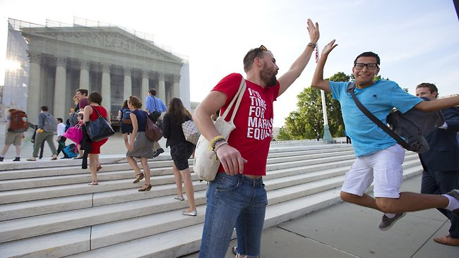 Gay rights activist Bryce Romero, who works for the Human Rights Campaign, offers an enthusiastic high-five to visitors getting in line to enter the US Supreme Court.