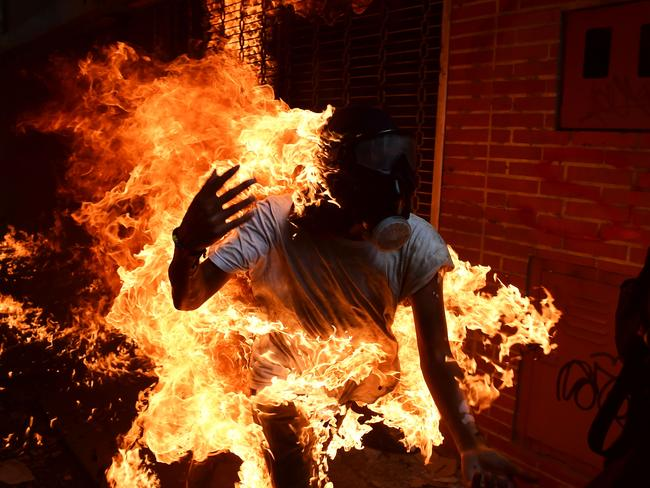 A demonstrator catches fire during clashes with riot police in a protest against Venezuelan President Nicolas Maduro, in Caracas. Picture: Ronaldo Schemidt.