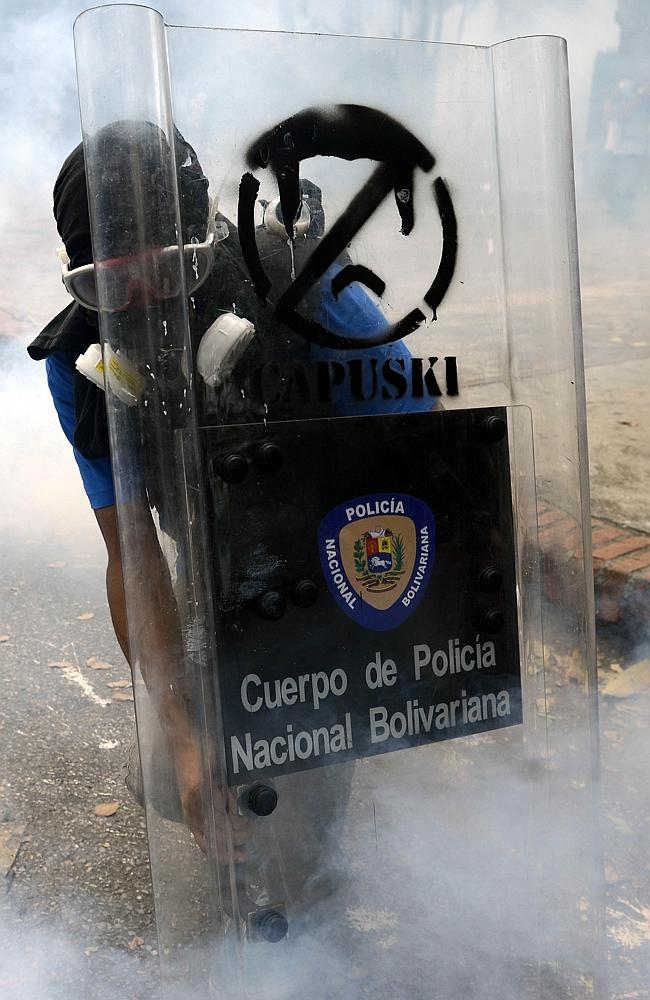 A Venezuelan student protects himself ... with a police shield during a protest. Picture: AFP/ Leo Ramirez