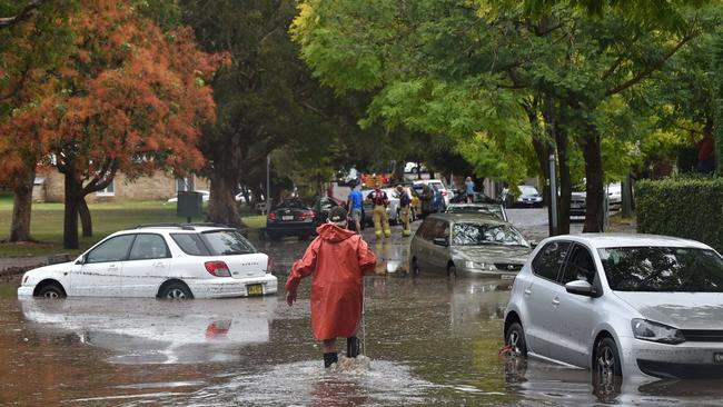 A worker wades past inundated cars on a flooded street after the second storm hits the eastern suburbs of Sydney. Image: AFP/ Peter PARKS