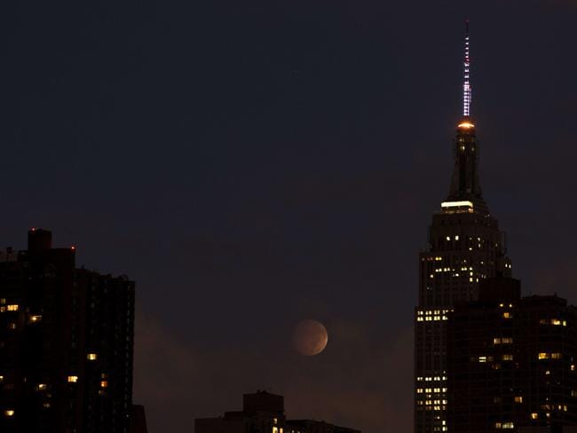 Never sleeps ... the total eclipse is seen through clouds near the Empire State Building in New York. Picture: AFP PHOTO/Stan HONDA