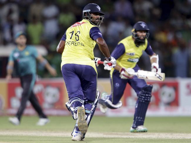 World XI batsman Hashim Amla, right, runs between the wickets with his partner Thisara Perera.