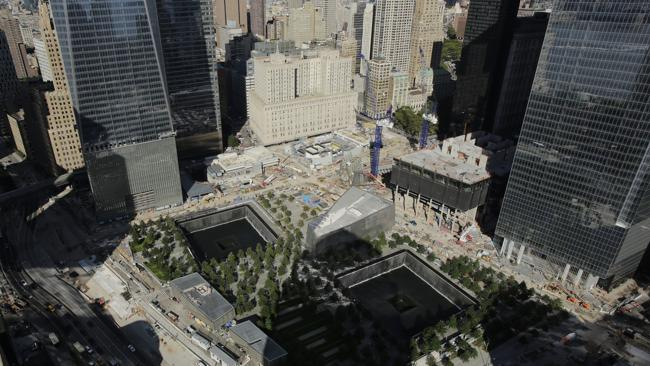 The wedge-shaped pavilion entrance of the National September 11 Museum is located between the square outlines of the memorial waterfalls at the World Trade Center. (AP Photo/Mark Lennihan)