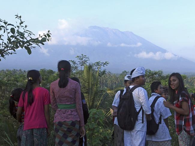 Residents observe the Mount Agung from a viewing point in Bali, Indonesia, Wednesday, Sept. 20, 2017. Officials have more than doubled the size of the evacuation zone around the Mount Agung volcano on the tourist island of Bali and raised its alert level for the second time in less than a week. (AP Photo/Firdia Lisnawati)