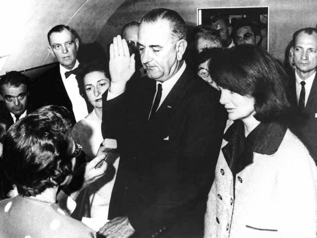 Jackie Kennedy looks on as Vice-President Lyndon Johnson is sworn in as president on the plane back to Washington DC.