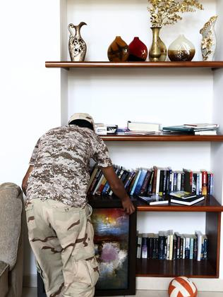 'Preventing looting' ... member of the Fajr Libya (Libya Dawn) Islamist militia holds an artwork in the living room of a villa at the US diplomatic compound in the Libyan capital Tripoli. Picture: Mahmud Turkia