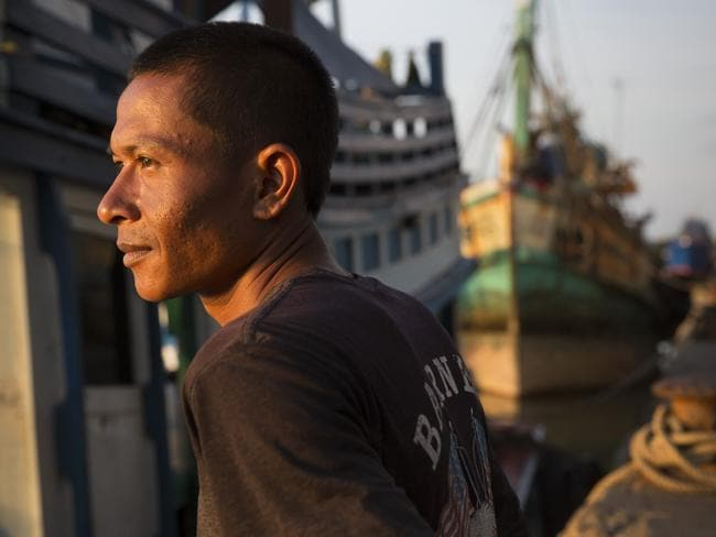 A fishing boat worker rests while his boat is at the port in Songkhla, Thailand. Picture: Paula Bronstein