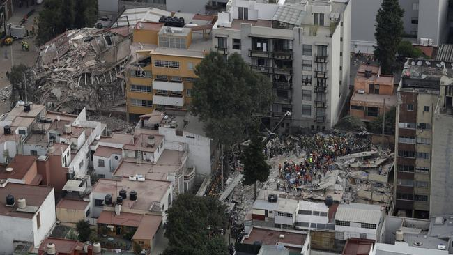 Rescue workers search for people trapped inside a collapsed building, with another collapsed building in the background, in the Del Valle area of Mexico City, Wednesday, September 20, 2017. Picture: Rebecca Blackwell/AP
