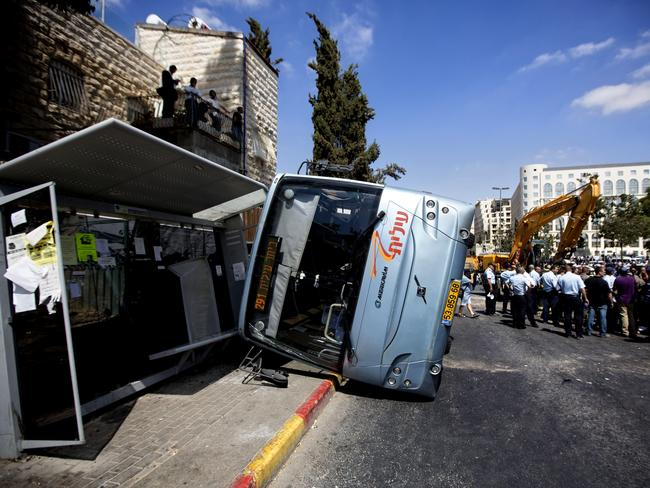 Attack ... A damaged bus flipped over after a Palestinian man rammed into it with an excavator in Jerusalem. Picture: AP
