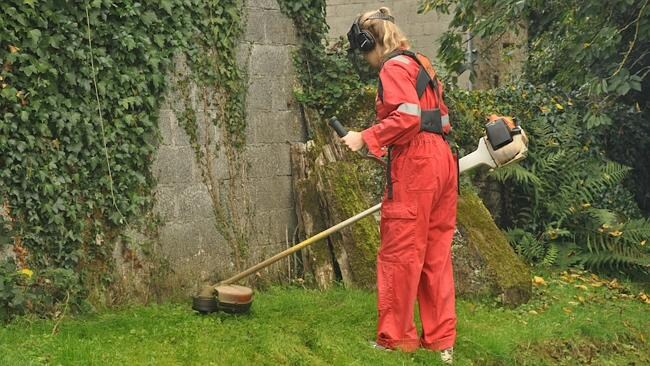 Laura using an industrial whipper-snipper to trim the grass.
