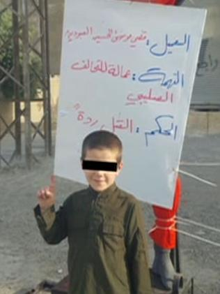 The youngest son of Khaled Sharrouf poses with the body of a man hanging from a metal cross.