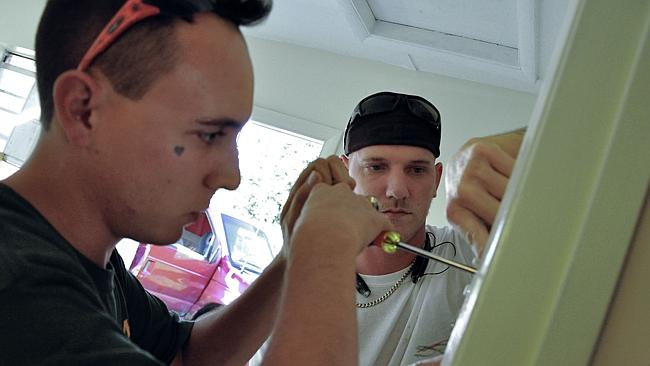 Registered sex offenders David Woods (right) and Matthew Richey fix electric wiring in a house for future residents of the community. Picture: AFP