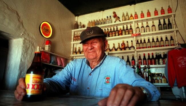 Betoota Hotel publican Sigmund Remienko, 82, behind bar with bottle of beer on eve of his retirement.